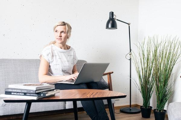 Nainen vuokra-asunnon sohvalla kannettavan tietokoneen kanssa