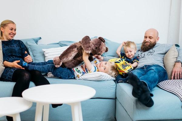 Lapsiperhe rentoutuu vuokra-asunnon sohvalla