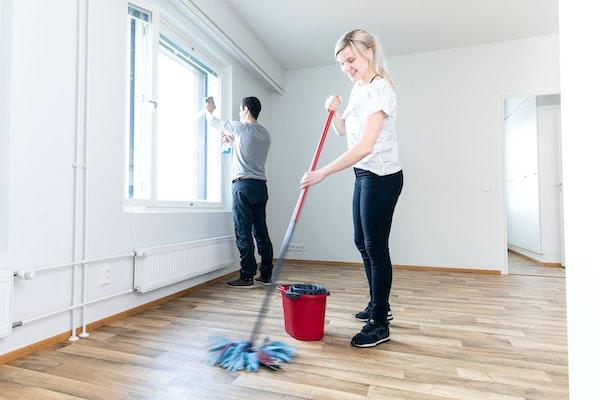 Mies ja nainen siivoavat vuokra-asuntoa