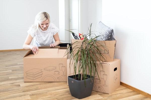 Nainen pakkaa muuttolaatikko vuokra-asunnossa