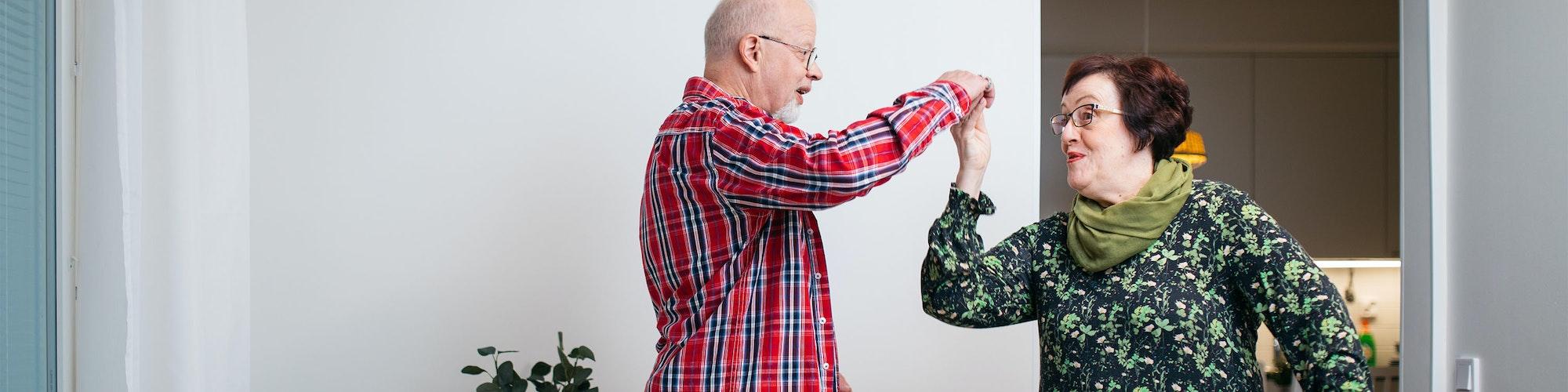 Seniori-pariskunta tanssii vuokra-asunnon olohuoneessa