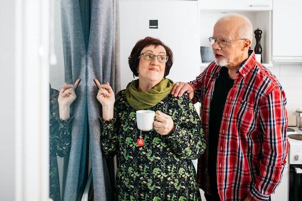 Seniori-pariskunta katselee ulos vuokra-asunnon ikkunasta