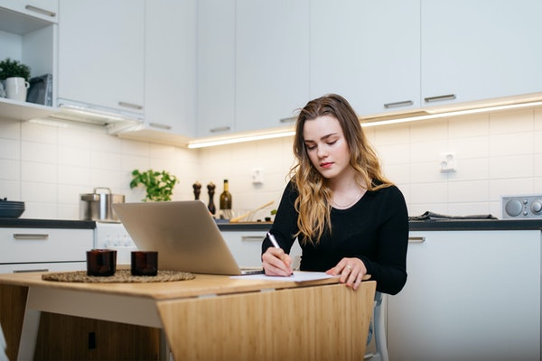 Nuori nainen tekee töitä kannettavalla tietokoneella vuokra-asunnon keittiön pöydän ääressä
