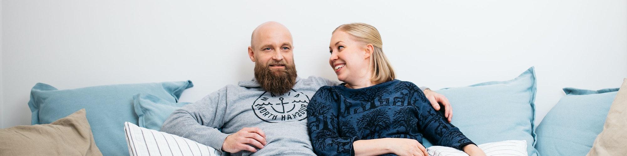 Perheen isä ja äiti rinnakkain vuokra-asunnon sohvalla