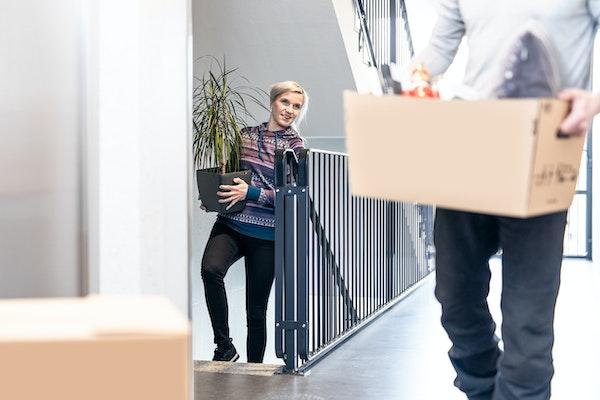 Nuori pariskunta kantaa muuttotavaroita vuokra-asunnon rappukäytävässä