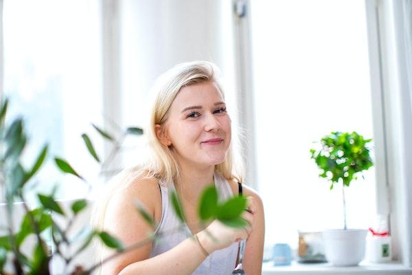 Nuori nainen syömässä vuokra-asunnon valoisassa keittössä