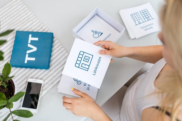 Nuori nainen selaa asumiseen liittyviä aihekortteja vuokra-asunnon pöydän ääressä