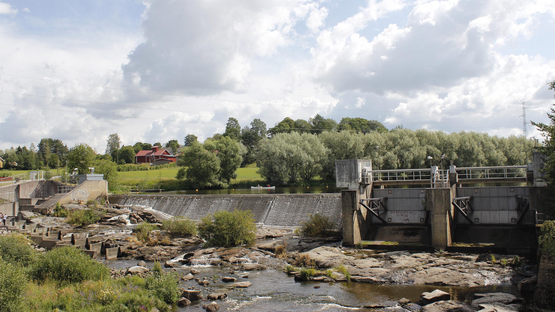 Kuvassa Halistenkoski, jossa padosta juoksee hieman vettä. Taustalla vihreä niitty ja punainen talo