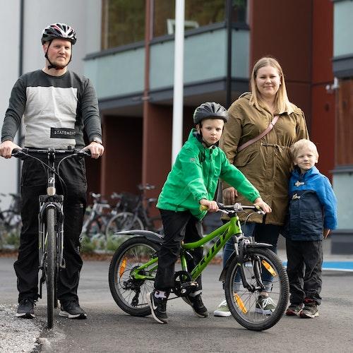 Kuvassa perhe Hirvensalon Arolassa ulkoilemassa kerrostalon edustalla
