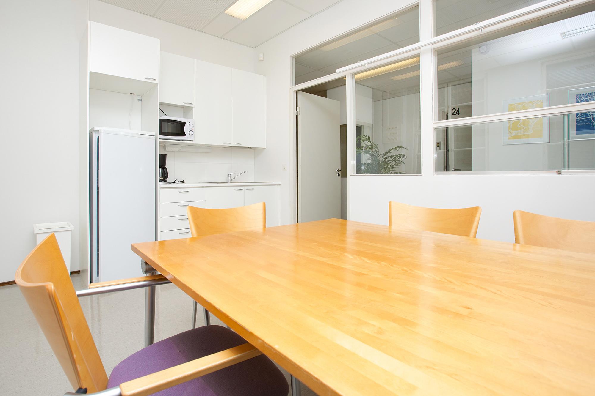 Kuvassa toimistohotellin kokoushuone ja keittiö