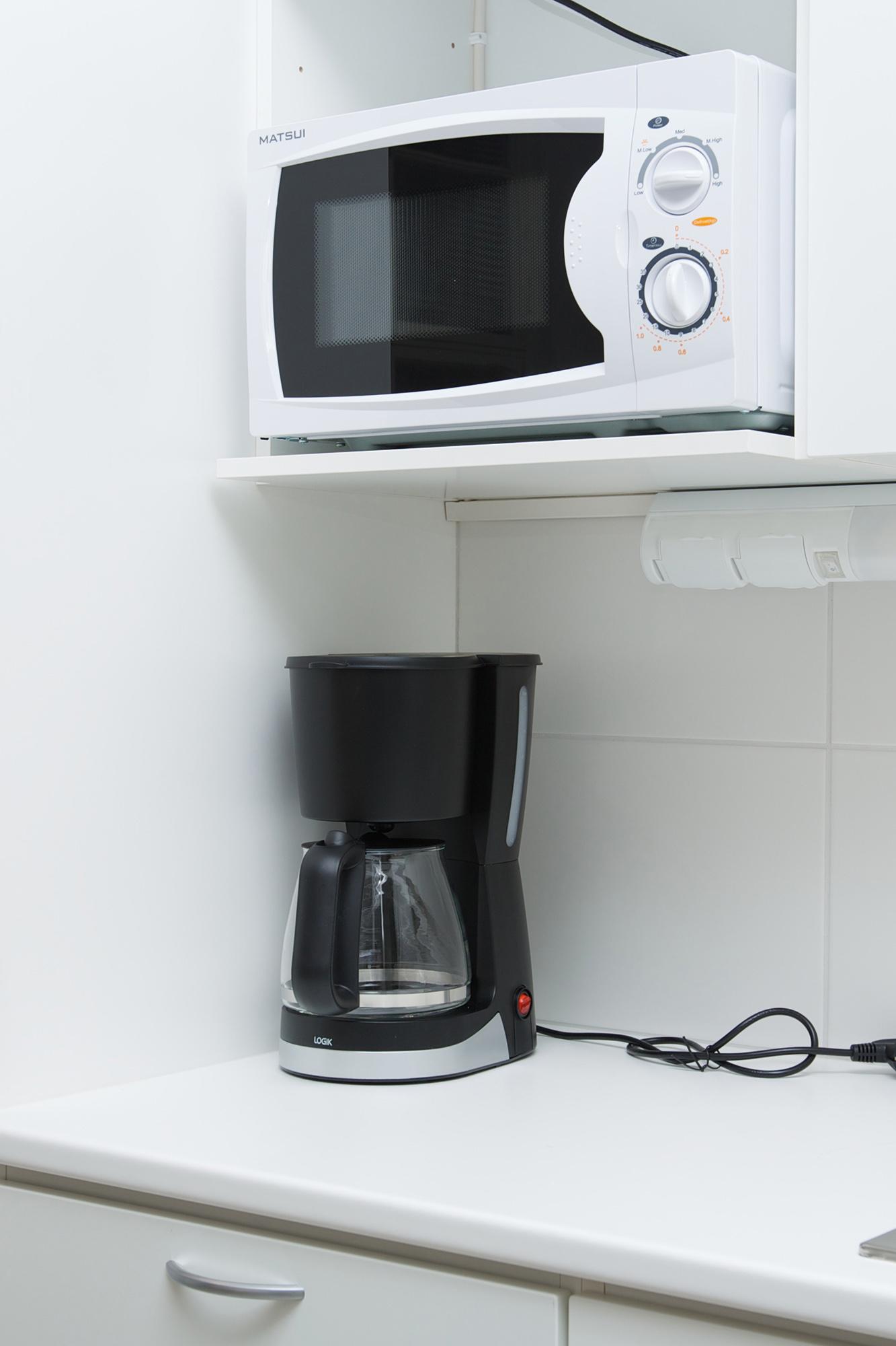 Lähikuva toimistohotellin keittiöstä, kahvinkeitin ja mikroaaltouuni
