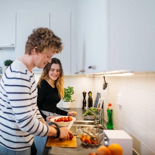 Nuoripari laittaa ruokaa keittiössä