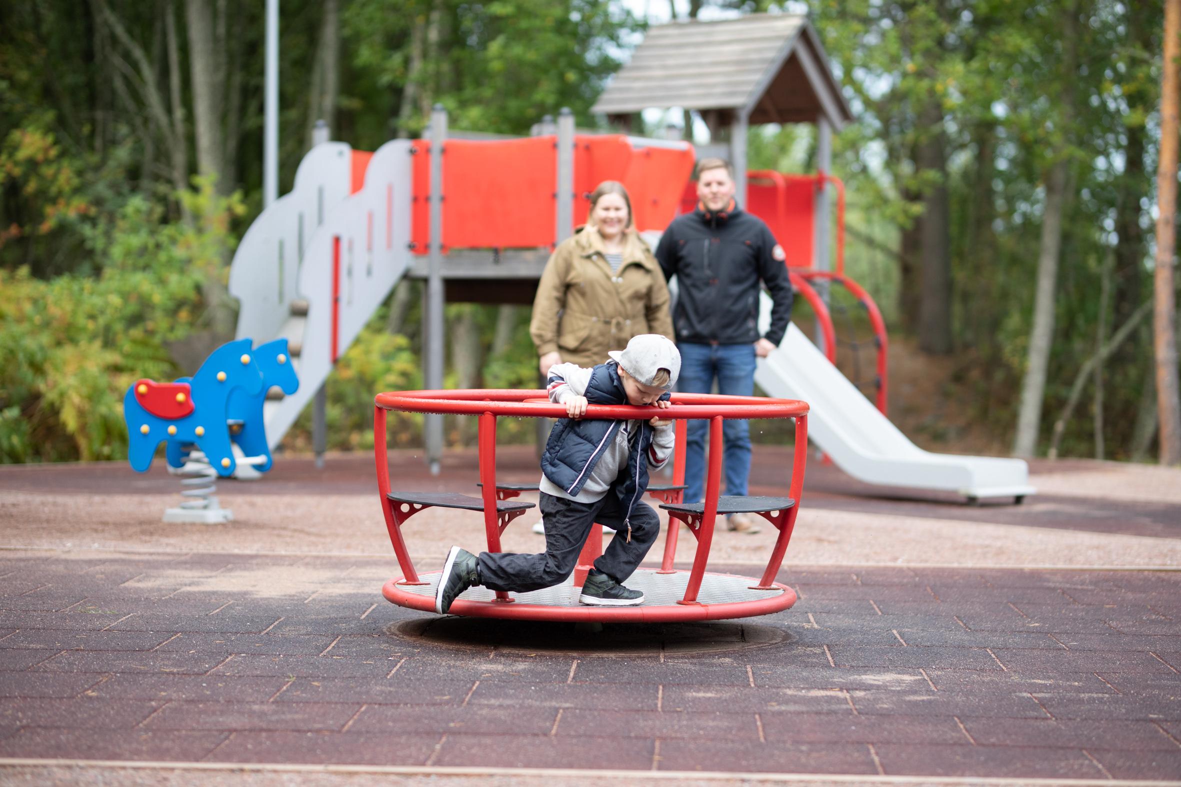 Perheen lapsi karusellissa.
