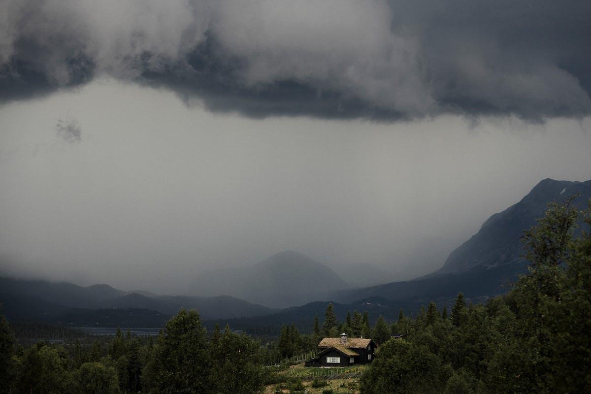 hytte i fjellet med dramatiske skyer