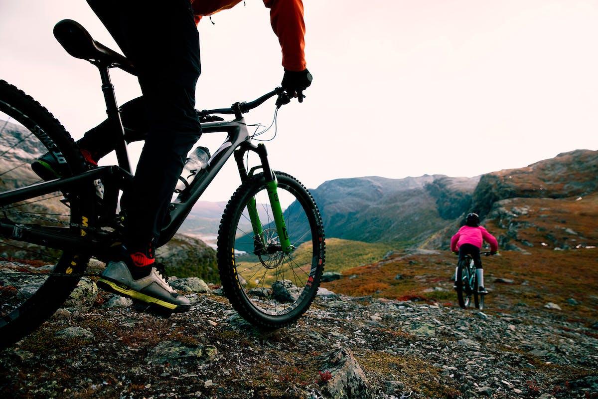 to stisyklister på vei ned fra fjellet