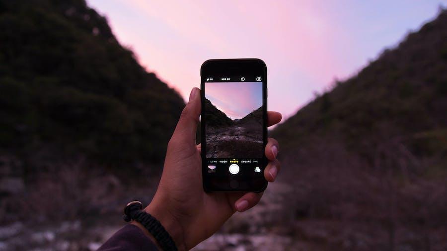 Person som tar bilde av vakker natur med smarttelefon