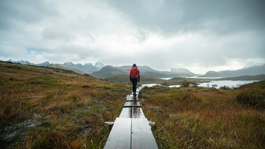 Regn gir lavere strømpriser. Kvinne som vandrer i fjellet i høstregn.