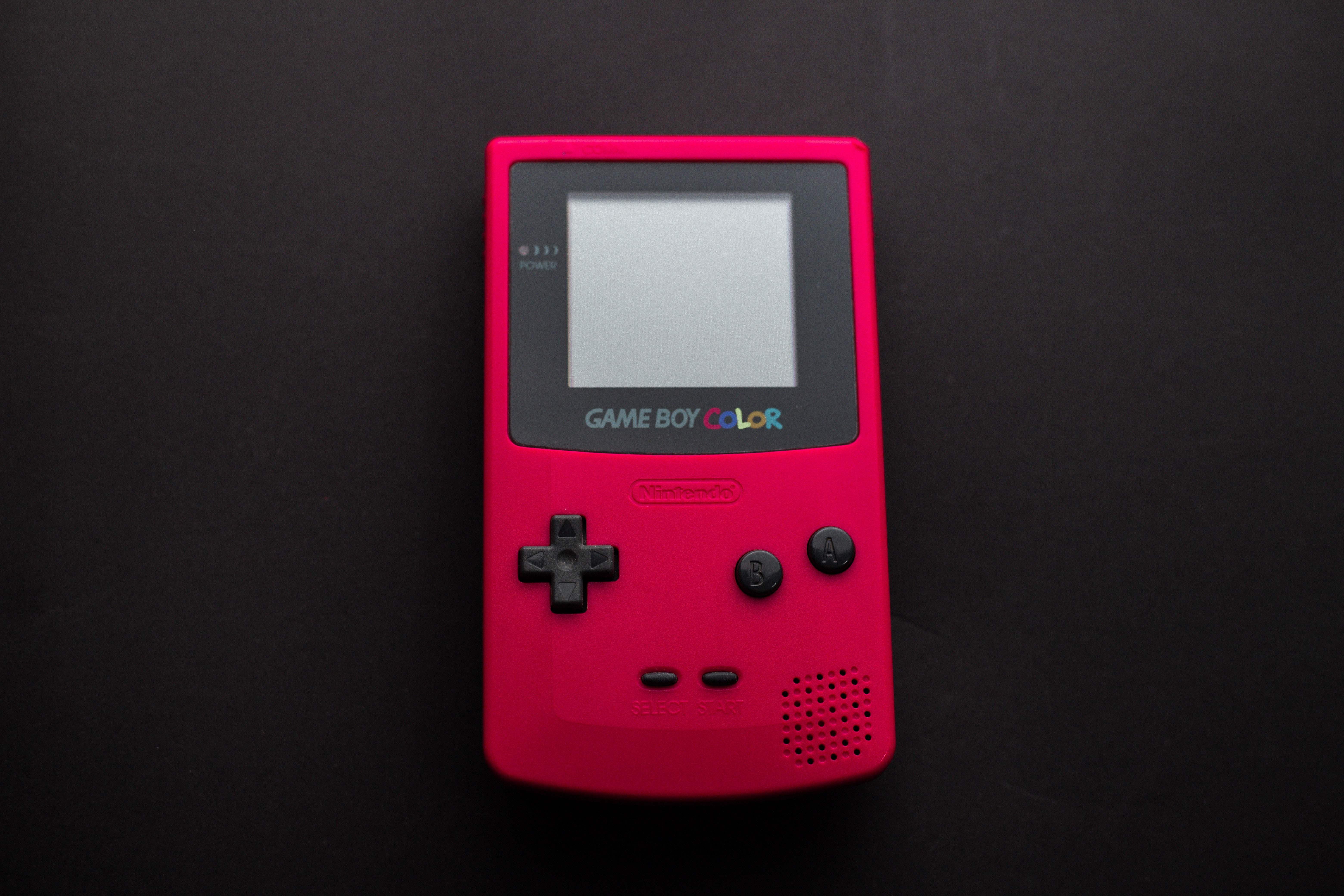 White Nintendo Game Boy with buttons in black, pink and grey colors