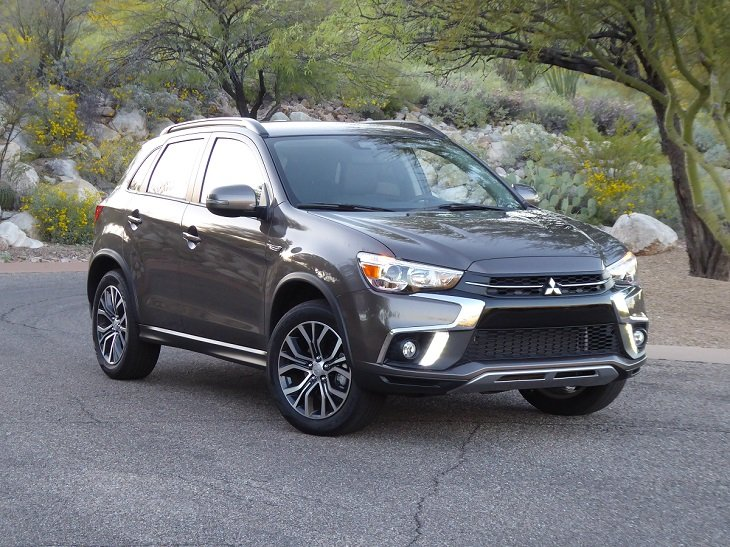 A smokey black Mitsubishi Outlander Sport S parked on a road in the wilderness