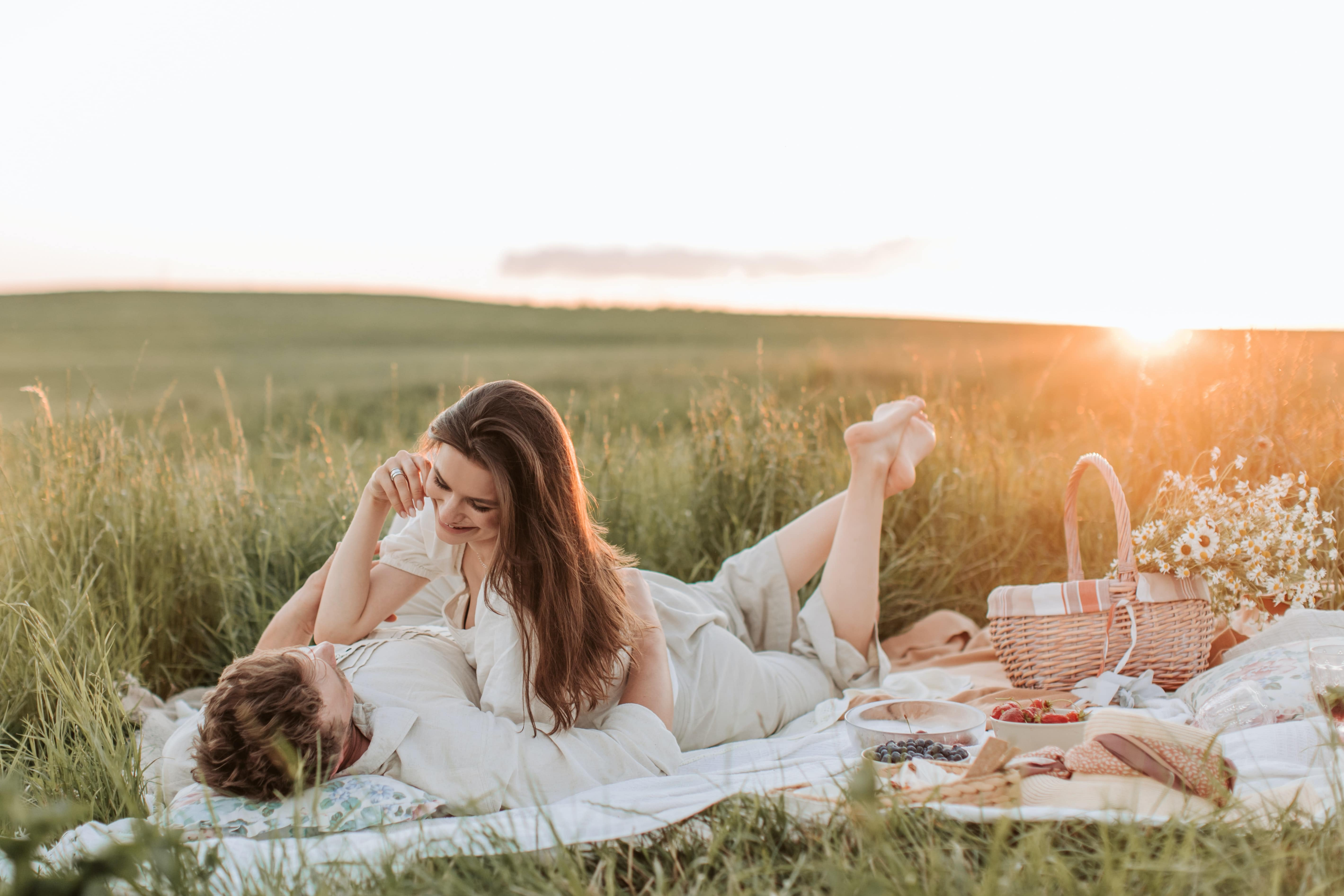 Man and woman lounging around with a picnic basket on grass