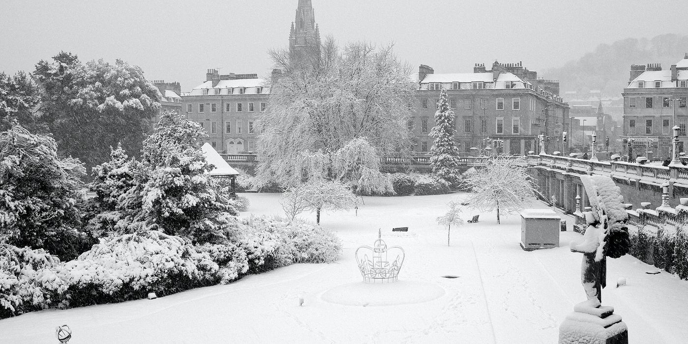 Bath England. Snow scene of the Royal Victoria Park, Bath England. Statues, bushes, grass, buildings all covered in snow.