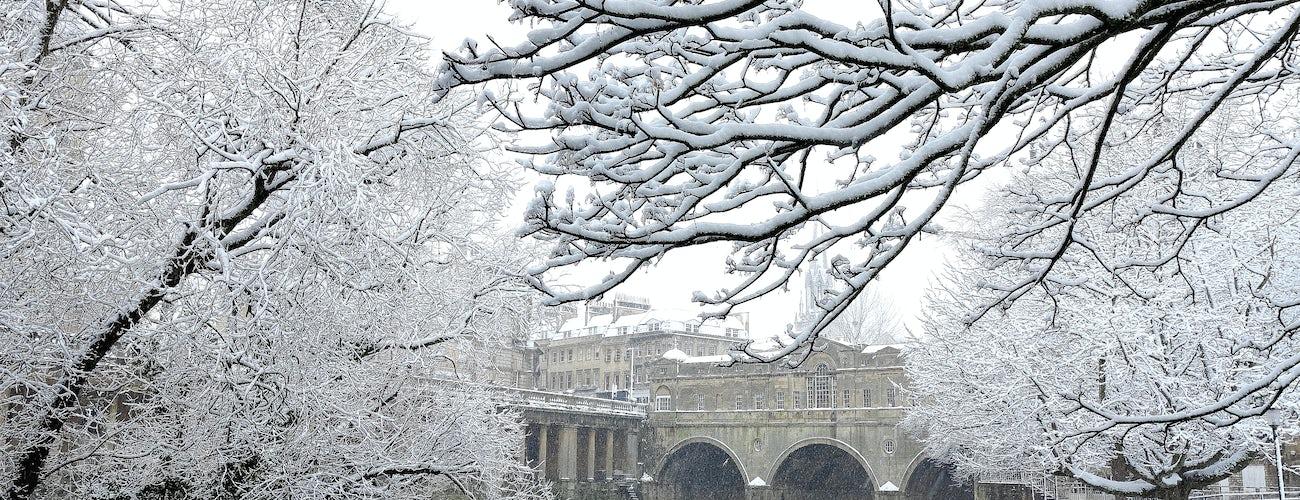 Bath, England a snowy scene showing weir of river Avon and Pulteney Bridge
