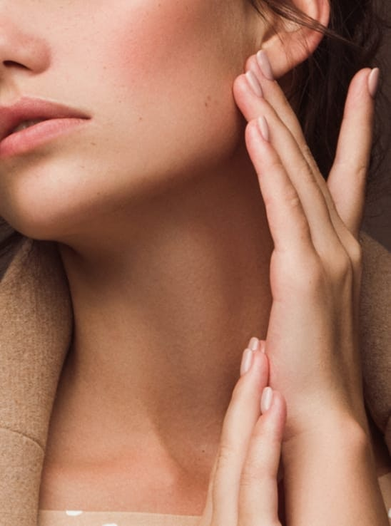 Woman's hands touching her jaw line and beautiful neck.