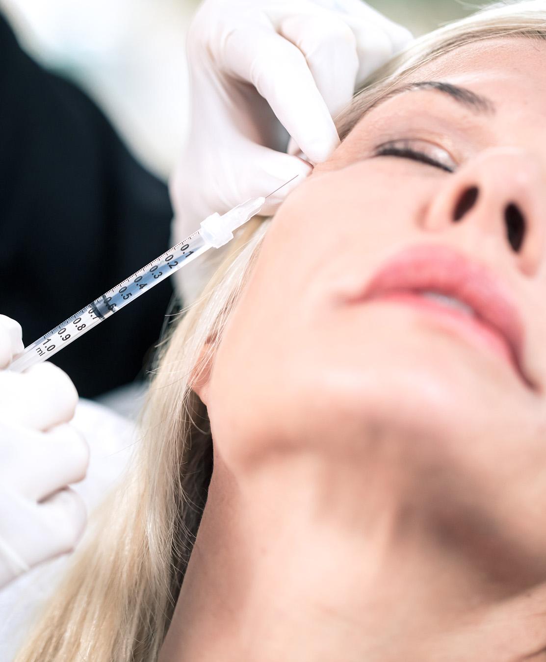 Older woman getting neuromodulators injected in face