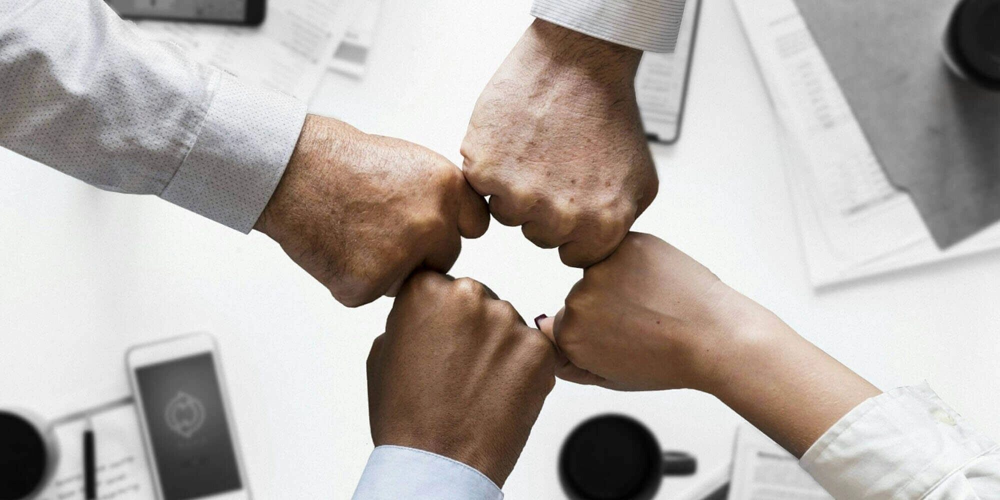 four fists of four people meeting representing camaraderie