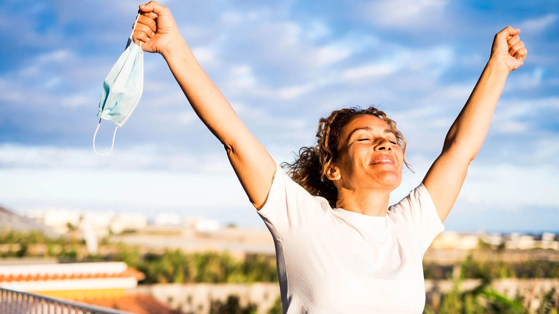 happy woman with open arms raised to the sky with mouth cover in hand