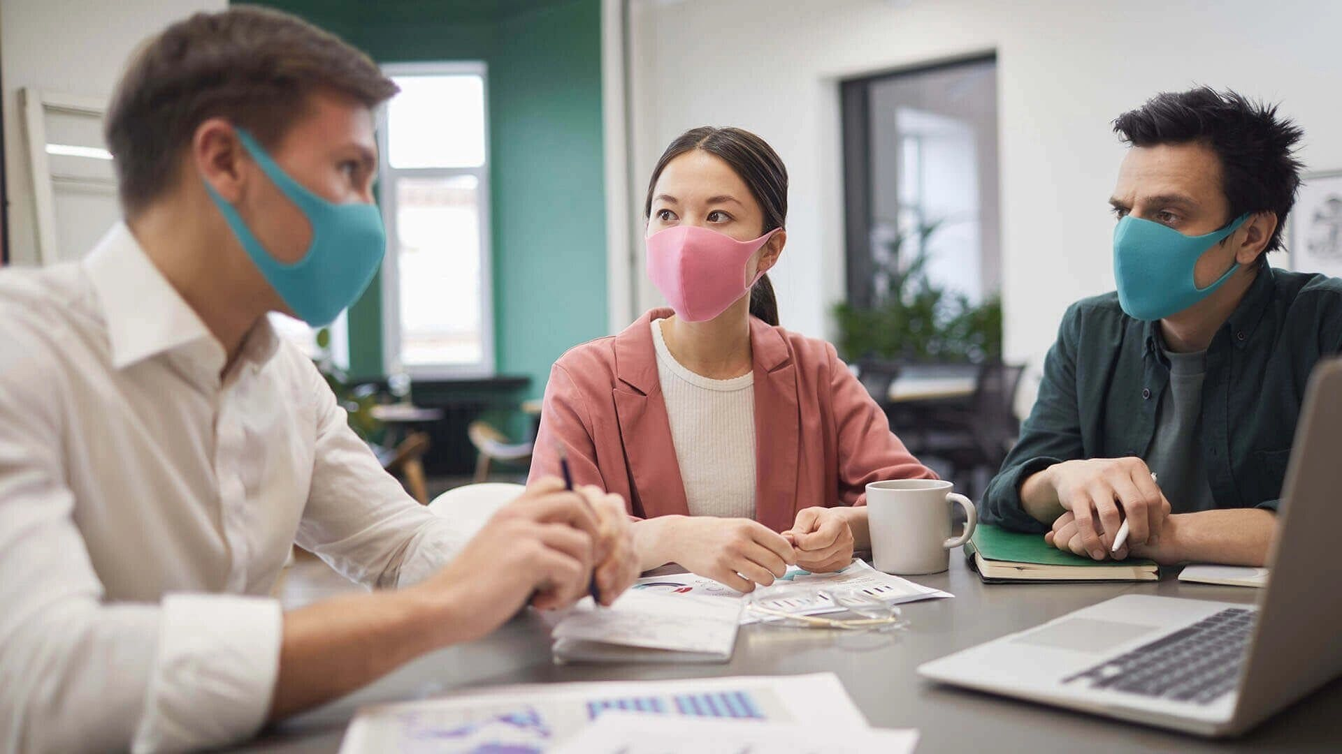 three people with mouth covers talking at desk