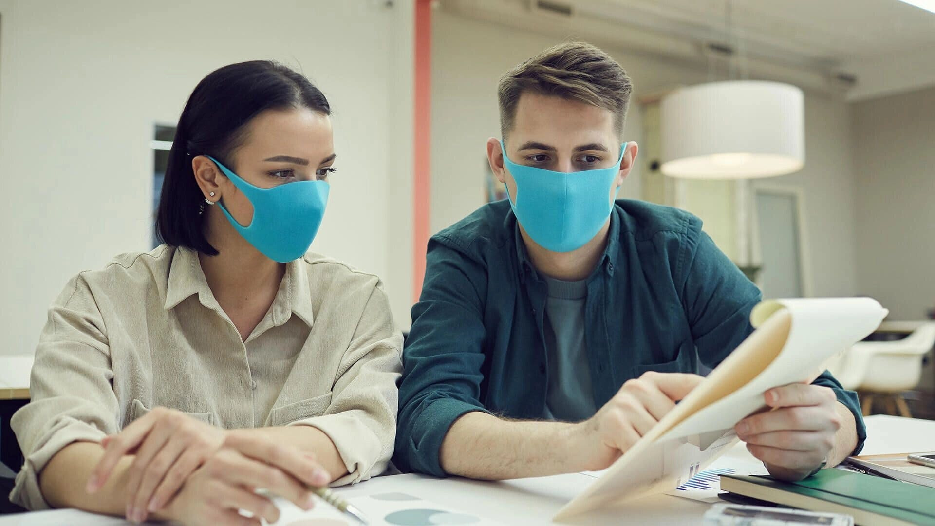 woman and man with mouth covers looking at a notepad