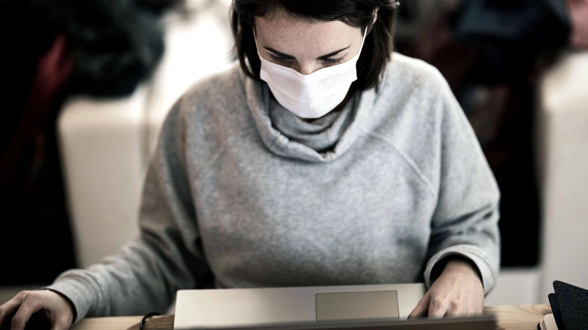 woman working with mouth cover on laptop