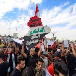 """حضور معترضین عراقی در خیابان، به مناسبت اولین سالگرد یک جنبش گستردهی ضد دولتی؛  معترضان خواستار اخراج کل طبقهی حاکم ِ متهم به فساد بودند؛ شهر مقدس نجف، ۴ آبان ۱۳۹۹/ ۲۵ اکتبر ۲۰۲۰. روی این سازه به زبان عربی نوشته شده است:""""عراق به عراقیان تعلق دارد، جایی برای مفسدان نیست."""" هزاران عراقی به سمت میدان بزرگ التحریر بغداد، و منطقهی سبز حرکت کردند تا اولین شورش ادامهدار علیه طبقهی کساد سیاسی کشور را جشن بگیرند. (عکس از گتی ایمیجز)"""