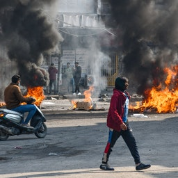 Iraqi protesters are pictured next to burning tires during clashes with police in the city of Nasiriyah on Jan. 10, 2021. (Photo via Getty Images)
