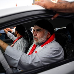 Iraqi cleric Muqtada Al-Sadr drives a car as he joins anti-government demonstrators gathering in the holy city of Najaf on Oct. 29, 2019. (Photo via Getty Images)