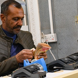An employee of a currency exchange counter counts bank notes in the southern Iraqi city of Nasiriyah on Dec. 20, 2020. (Photo via Getty Images)