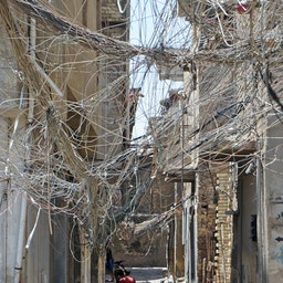 Iraqis walk beneath a web of electric wires in the capital Baghdad, on July 13, 2020. (Photo via Getty Images)