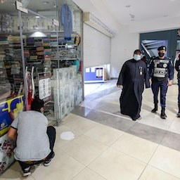 Policemen enforce COVID-19 restrictions in Kuwait City on Feb. 10, 2021 (Photo via Getty Images)
