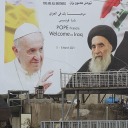 An Iraqi security guard stands in front of a billboard bearing portraits of the Pope and Ayatollah Ali Sistani in central Baghdad on March 4, 2021. (Photo via Getty Images)
