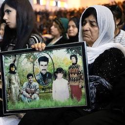 یک کرد عراقی با تصاویری از بستگاناش که در حمله شیمیایی حلبچه توسط نیروی هوایی صدام حسین کشته شدند. (عکس از گتی ایمیجز)