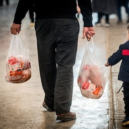 An Iranian man carrying two bags of reduced price chickens, Tehran, March 16, 2021. (Photo by Erfan Kouchari via Tasnim News Agency)