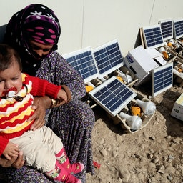 A displaced woman and her grandson sit next to solar power panels in a refugee camp in Erbil, Iraq on Feb. 1, 2015. (Photo via Getty Images)