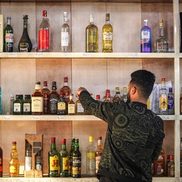 کارمند یک فروشگاه مشروبات الکلی در حال مرتبسازی بطریها؛ منطقهی باتاواین، بغداد، پایتخت عراق، ۱۵ آذر ۱۳۹۹/ ۵ دسامبر ۲۰۲۰ (عکس از گتی ایمیجز)