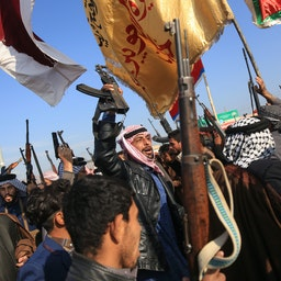 Armed tribesmen lift their guns as they take to the streets in a show of force amidst ongoing anti-government protests in southern Iraq. Dec. 8, 2019 (Photo via Getty Images)
