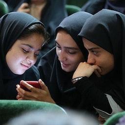 سه دختر جوان ایرانی که به صفحه ی یک گوشی هوشمند چشم دوخته اند. البرز، تهران. ۱۳ مرداد ۱۳۹۸. (عکس از خبرگزاری ایرنا)
