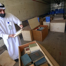 Government employee in Kuwait City inspects boxes containing archives seized during Iraq's 1990 invasion of Kuwait, on March 28, 2021. (Photo via Getty Images)