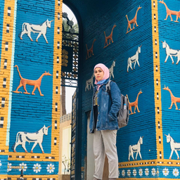 Young Iraqi archeologist Raya Nassif at a replica of the Ishtar Gate in Babylon, Iraq. (Photo via author)
