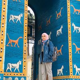 باستانشناس جوان عراقی، ریا نصیف، در کنار ماکت دروازه ایشتار در بابل، عراق. (عکس از نویسنده)