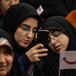 طالبتان إيرانيتان تنظران إلى هاتف محمول خلال مؤتمر في جامعة العلامة الطباطبي. طهران، ايران. 7 ديسمبر/كانون الأول 2019 (تصوير بهنام توفقي فروهر عبر وكالة مهر الإخبارية)